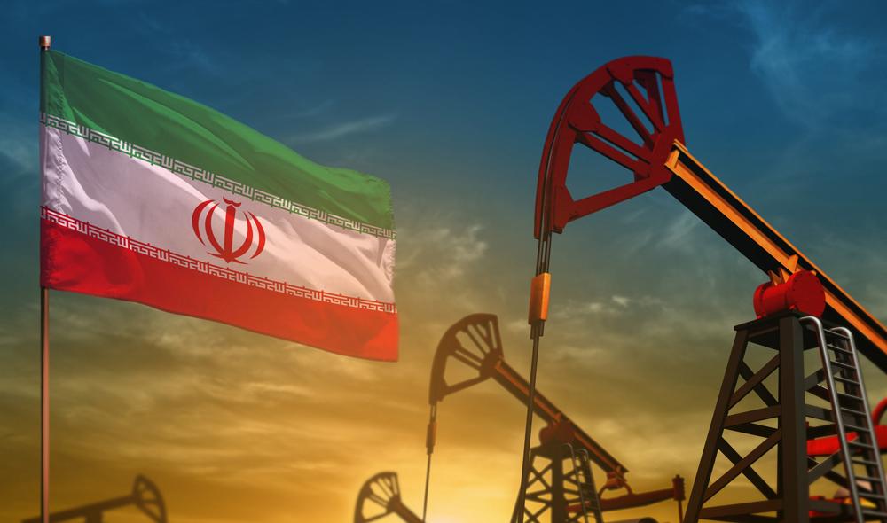 Iranische Flagge vor Förderanlagen im Sonnenuntergang