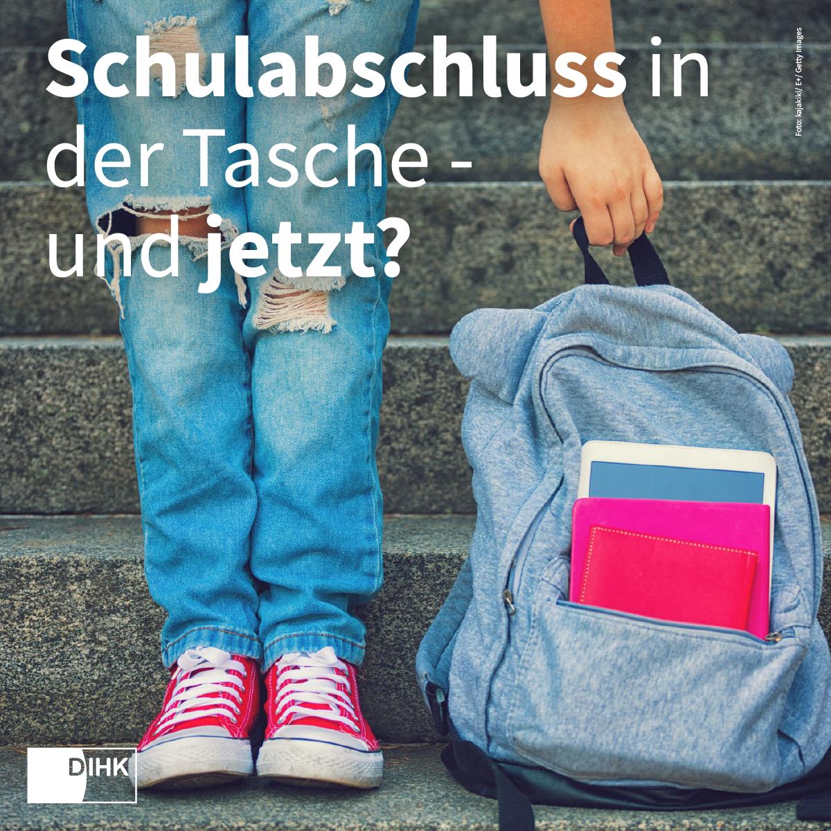 Beine einer/eiens Jugendlichen mit zerrissenen Jeans, der/die auf einer Treppe neben einem Schul-Rucksack steht