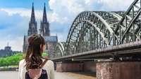 Chinesische Touristin blickt auf Deutzer Brücke und den Kölner Dom