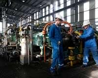 Ausbilder und Azubi arbeiten zusammen an einer Maschine.