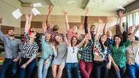Eine Gruppe von Jugendlichen freut sich und wirft Papiere in die Luft.