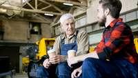 Älterer Arbeiter im Gespräch mit jungem Kollegen