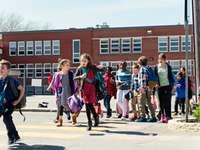 Gruppe von Schülern überquert Zebrastreifen