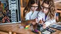 Zwei Mädchen schrauben an einem PC-Bauteil