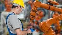 Arbeiter stellt Roboterarm über ein Tablet ein.