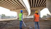 Männer in Sicherheitswesten, vermutlich Ingenieure, stehen unter dem Rohbau einer Brücke