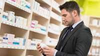 Mann blickt im Drogeriemarkt auf ein Medikament