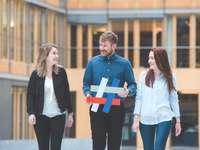 drei DIHK-Azubis laufen mit dem bunten Gemeinsam-Hashtag durch das Atrium des Hauses der deutschen Wirtschaft