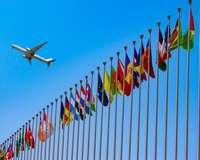 Flugzeug fliegt über viele Fahnenmasten mit verschiedenen Länderflaggen