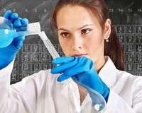 Chemikerin füllt eine blaue Flüssigkeit ins Reagenzglas