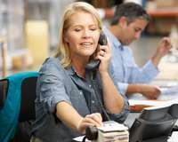Büroangestellte am Telefon und sucht Visitenkarte