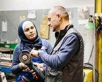 Ein Techniker erklärt einer weiblichen, muslimischen Auszubildenden in einer Werkstatt eine Mühle