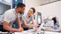 Zwei Ingenieure, ein Mann und eine Frau, besprechen sich am Laptop in einer Werkshalle vor Maschinen und Maschinenteilen.