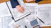 Hand mit Stift über einem Tisch mit Taschenrechner und vielen Steuerunterlagen