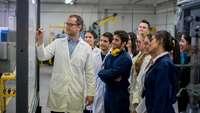 Gruppe von Studenten mit Dozent in einer Werkshalle