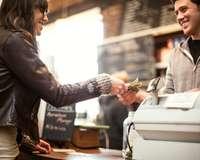 Frau bezahlt mit Bargeld an Registrierkasse