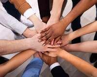 Übereinanderliegende Hände mit verschiedenen Hautfarben