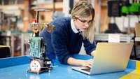 Junge Frau beugt sich neben einer kleinen Roboter-Installation über einen Laptop