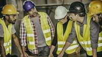 Besprechung internationaler Fachkräfte auf einer Baustelle