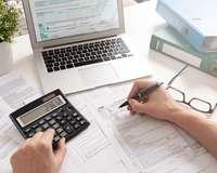 Steuerformulare auf einem Tisch und auch im PC, Hände bedienen einen Taschenrechner und füllen Formulare aus