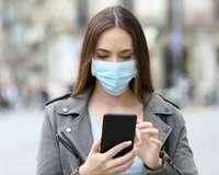 Junge Frau mit Mundschutz schaut auf ihr Mobiltelefon