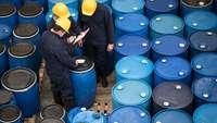 Arbeiter mit Mundschutz überprüfen blauen Chemikalienfässer