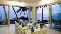 Blick aus einem Esszimmer mit gedecktem Tisch auf eine Bucht mit Palmen
