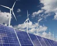 Solarkollektoren und Windräder vor blauem Himmel