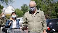 Menschen mit Masken und Einkaufswagen stehen in einer Schlange