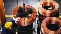 Arbeiter und Rollen mit Kupferkabeln von oben