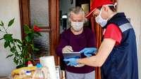 Älterer Frau quittiert einem jungen Mann auf dem Tablett den Empfang einer Kiste Lebensmittel, beide mit Mundschutz