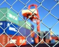 Container und Kran hinter einem Maschendrahtzaun