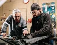 Zwei Männer beugen sich über den Motor eines Autos