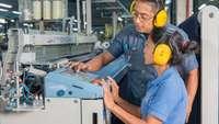 In einer Fabrik in Ecuador erklärt ein Ausbilder einer jungen Frau eine Maschine