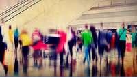 Bewegungsunscharf fotografierte Menschenmenge vor der Rolltreppe in einem Einkaufszentrum