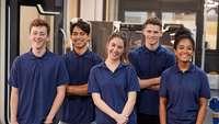 fünf junge Menschen stehen beisammen und lachen in die Kamer