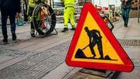 Baustelle mit großem Warnschild und Bauarbeitern