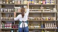 Geschäftseröffnung: Frau räumt Feinkost ins Regal