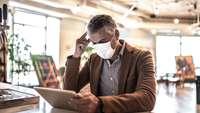 Mann im Anzug mit Mund-Nasen-Bedeckung sitzt vor einem Laptop