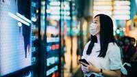 Chinesische Geschäftsfrau blickt in einer Passage auf einen öffentlichen Monitor mit Finanzdaten