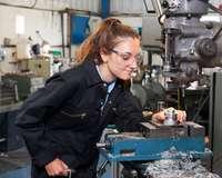junge Frau mit Schutzbrille und Blaumann an metallverarbeitender Maschine
