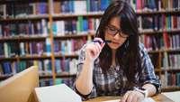 Junge Frau beim Studium von Büchern vor einem Bücherregal