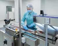 Frau sortiert in Produktion Tabletten.