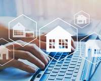 Hände auf Tastatur mit Immobilien-Symbolen