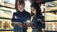 Zwei junge Menschen recherchieren auf dem Smartpad