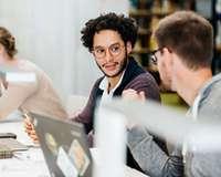 Zwei junge Männer am Laptop blicken einander an