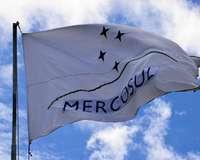 Flagge Mercosur / Mercosul weht im Wind vor blauem Himmel mit einzelnen Wolken