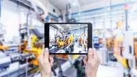 Hände mit Smartpad in einer Fertigungshalle