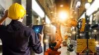 Mann überprüft Roboter per Tablet