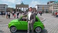 Torsten Wunderlich steht vor einem grünen Fiat vor dem Brandenburger Tor in Berlin